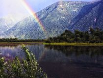 Rainbow over the creek. Stock Images