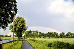 Rainbow over the crowns of the trees next to the bike path Stock Image