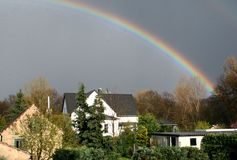 Rainbow over deutschland. A rainbow caught over a small german village stock images
