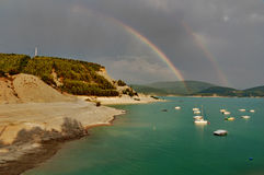 Rainbow over Embalse de Yesa. A view on the lake Embalse de Yesa in Spain featuring a double rainbow. This picture was taken from a campsite below the ghost town Royalty Free Stock Photos