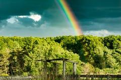 Rainbow over a farm field Stock Photo