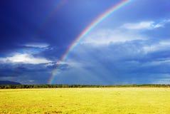 Rainbow over field Stock Photo
