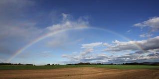 Rainbow over the field Stock Photos