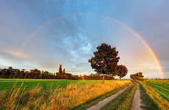 Rainbow over field road royalty free stock photography