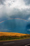 Rainbow over field road Royalty Free Stock Image