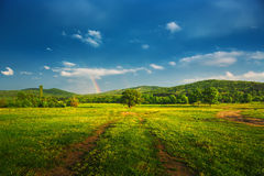 Rainbow over fields and trees on a farm Stock Photo