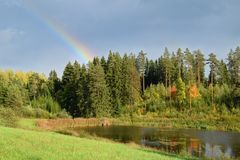 The rainbow over forest at countryside.