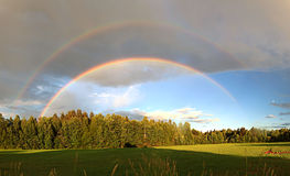 Rainbow over forest and field Stock Images