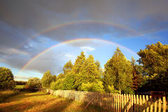 Rainbow over forest and field Stock Photos