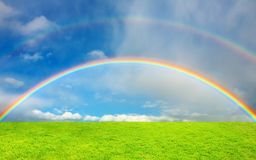 Rainbow over green field royalty free stock image