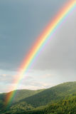 Rainbow over green hills Royalty Free Stock Image
