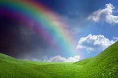Rainbow over green hills Stock Images