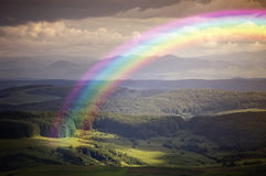 Rainbow over a green meadow near mountains in summer Royalty Free Stock Image