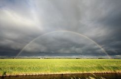 Rainbow over green meadow and river Stock Photography