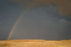 Rainbow over grey desert sky Stock Image