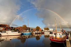 Rainbow over harbor in Zoutkamp Royalty Free Stock Photography