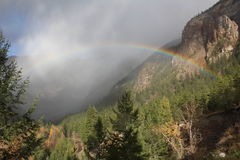 Rainbow over Hedley Creek. A rainbow arcs over Hedley Creek and disappears into the mist that has settled over the mountains on a sun dappled autumn day Royalty Free Stock Images