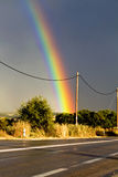 Rainbow over the highway. After a heavy storm Royalty Free Stock Photo