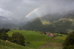 Rainbow over hills. Rainbow over meadow on a hill in Switzerland. Clouds and forested hills in the background Stock Photo