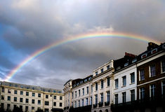 Rainbow over historic buildings in Brighton, United Kingdom. Rainbow in forming semicircle in stormy sky over historic regency buildings in Brighton City centre stock photos
