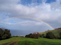 Rainbow over the island Stock Photos