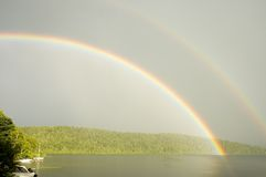 Rainbow over a lake 1. Prismatic colors of a rainbow over a lake stock photography