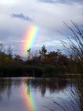 Rainbow over the lake. Clouds dispersing after rain Stock Photography