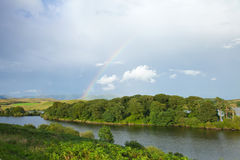 Rainbow over a lake Stock Images