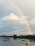 Rainbow over Lake with Clouds Stock Photography