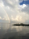 Rainbow over Lake with Clouds Royalty Free Stock Photo