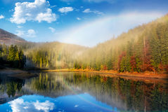 Rainbow over the lake in foggy spruce forest Stock Photography