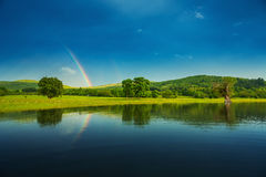 Rainbow over a lake, reflected in the water Royalty Free Stock Images