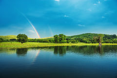 Rainbow over a lake, reflected in the water Royalty Free Stock Image