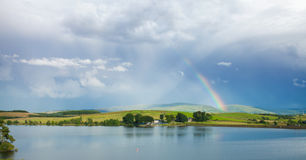 Rainbow over lake Stock Images