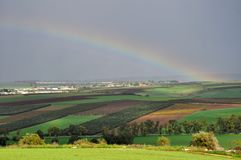 Rainbow over landscape, village and fields royalty free stock images