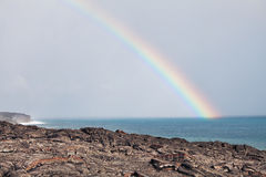 Rainbow over lava flow from erupting volcano Stock Photo