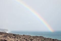Rainbow over lava flow from erupting volcano Royalty Free Stock Image