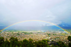 Rainbow over the Lijiang old town. The old town of Lijiang is also known as Dayan town in Lijiangba. It is an intact ancient city inhabited mostly by Naxi ethnic Stock Photography