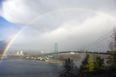 Rainbow Over Lions Gate Bridge. A rain cloud and sunlight results in a rainbow over Lions Gate Bridge in Vancouver, British Columbia Stock Photo
