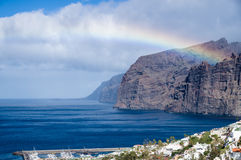 Rainbow over Los Gigantes cliffs and resorts Stock Image