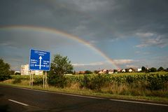 Rainbow over Mochov. A rainbow over a small Czech town of Mochov and a signpost Stock Photography