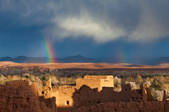 Rainbow over Morocco village in desert.  royalty free stock image