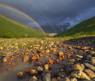 Rainbow over the mountain river Royalty Free Stock Photo