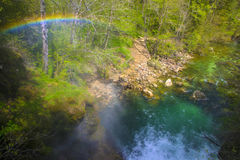 Rainbow over mountain stream flowing through gorge, Slovenia. Rainbow over mountain stream flowing through gorge. Vintgar Gorge near Bled, Triglav National park Royalty Free Stock Images