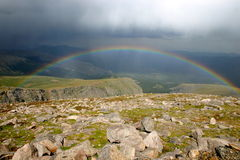 Rainbow over mountain valley Stock Images