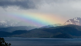 Rainbow Over Mountains. Rainbow reaches down to green mountains with ocean bay in fore ground Royalty Free Stock Photography