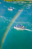 Rainbow over Niagara. Rainbow over tourist boats Maid of the Mist under Niagara falls royalty free stock photography