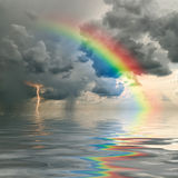 Rainbow over ocean. Colorful rainbow over ocean, thunderstorm with rain and lightning on background Stock Images