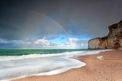 Rainbow over ocean coast by cliff Royalty Free Stock Photos
