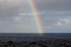 Rainbow Over Ocean and Rocky beach Stock Photos